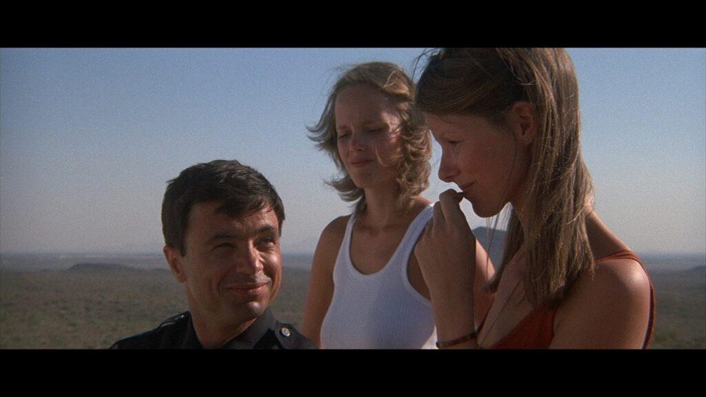 Polizist Jim, wir sehen nur den Kopf des kleingewachsenen Mannes, grinst zwei junge Frauen an - Electra Glide in Blue