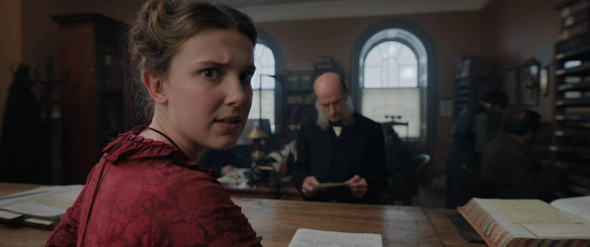 Enola (Millie Bobby Brown) wendet ihren Blick gen Zuschauer. Sie trägt ein rotes Kleid und sitzt an einem Schreibtisch hinter dem ein Mann mit Glatze steht.