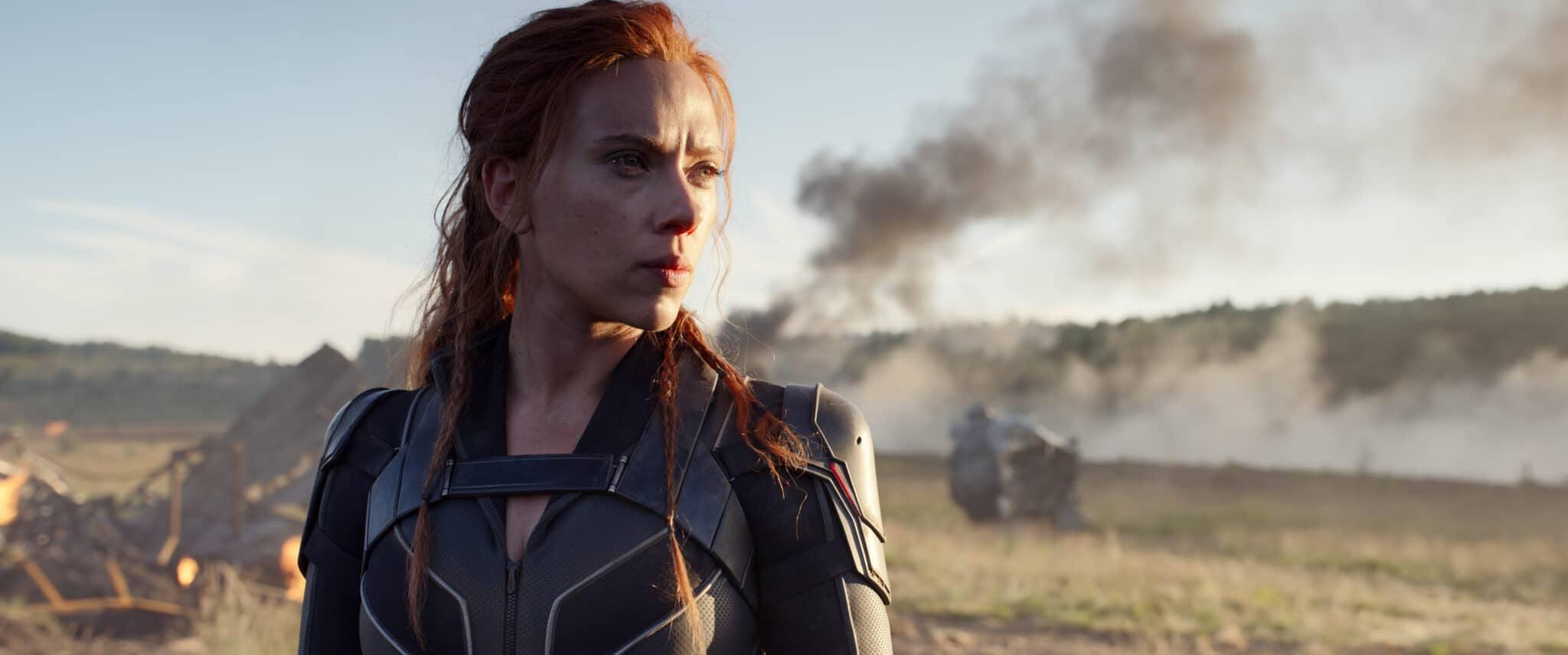 Black Widow (Scarlett Johansson) steht vor einigen Wrackteilen und Rauch auf einem offenen Feld.