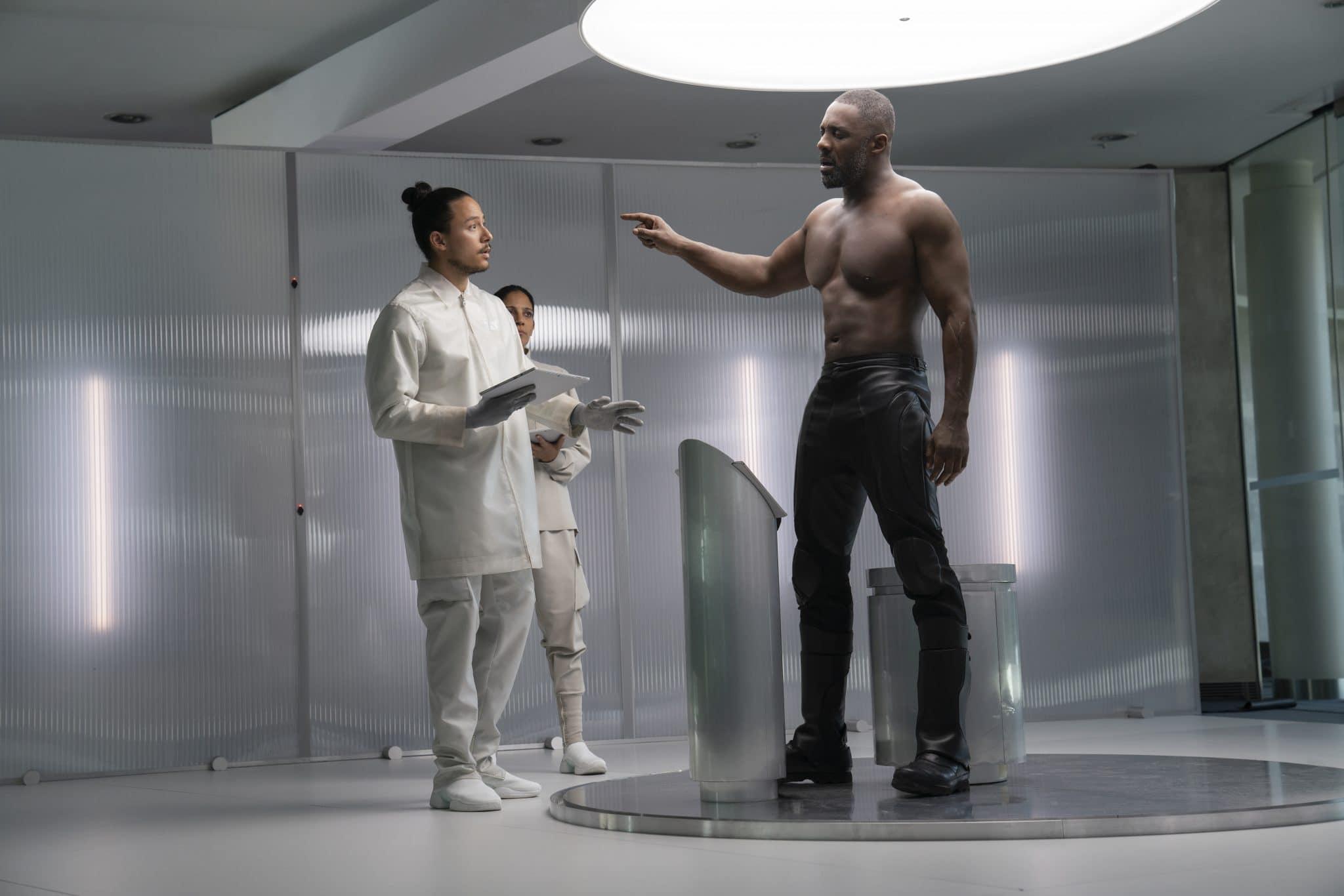 Brixton (Idris Elba) bedroht in einem sterilen Labor mit erhobenem Finger zwei Mitarbeiter in weißen Kitteln.