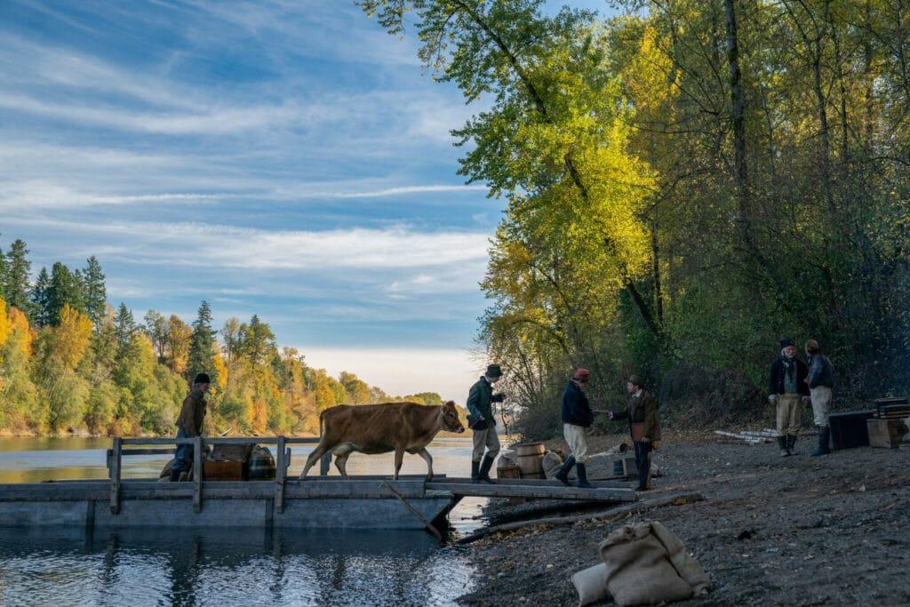 Eine Kuh wird von drei Männern über einen Steg an das Ufer begleitet, um es dort drei weiteren Männern zu verkaufen.