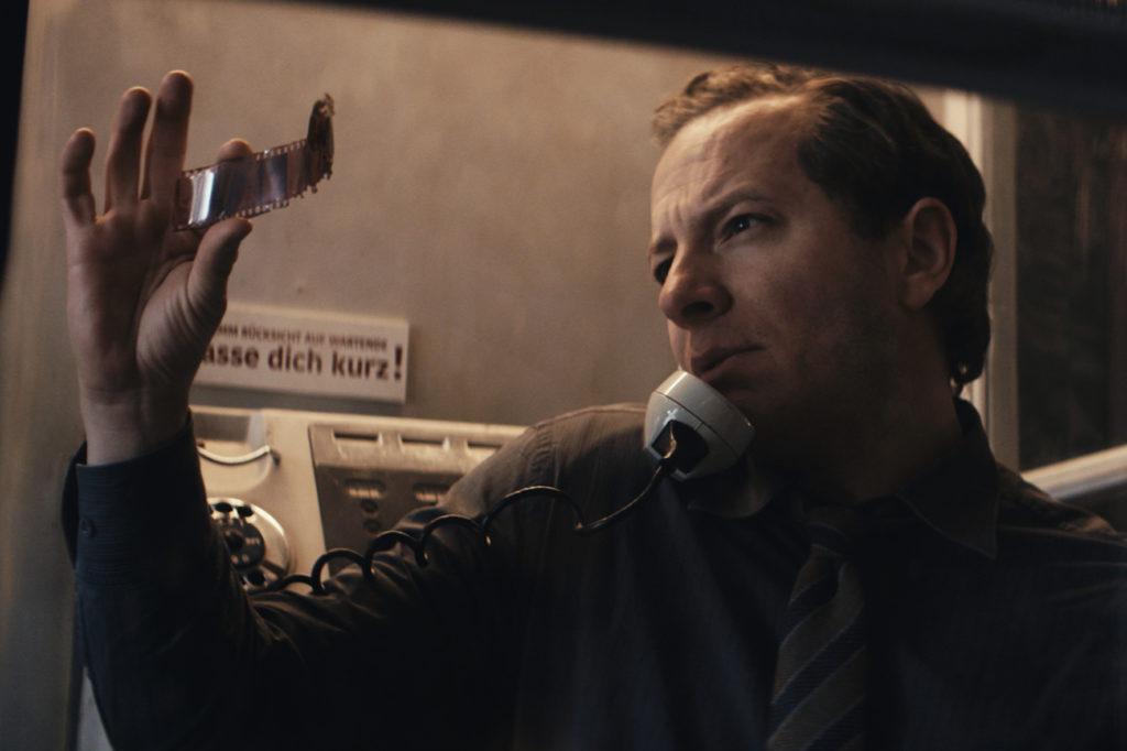 Kommissar Stein schaut sich mit Hörer am Ohr Film-Negative an in Freies Land