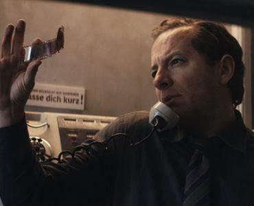 Kommissar Stein schaut sich Film-Negative an in Freies Land