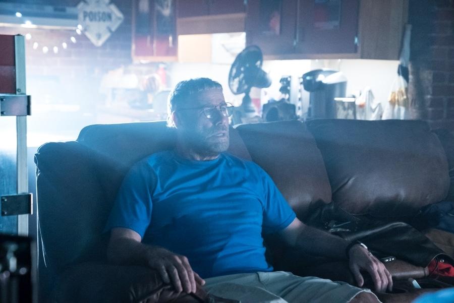 Moose (John Travolta) sitzt in The Fanatic auf seinem braunen Ledersofa und guckt in seinem Heimkino leidenschaftlich einen Horrorfilm.