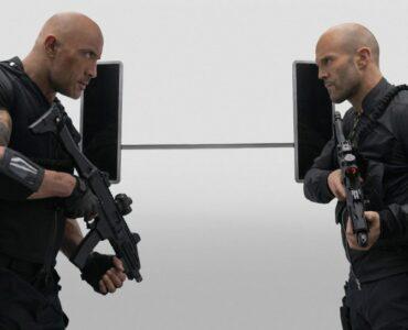 Dwayne The Rock Johnson und Jason Statham aus Fast & Furious Hobbs & Shaw stehen sich bewaffnet gegenüber und starren sich wütend an.
