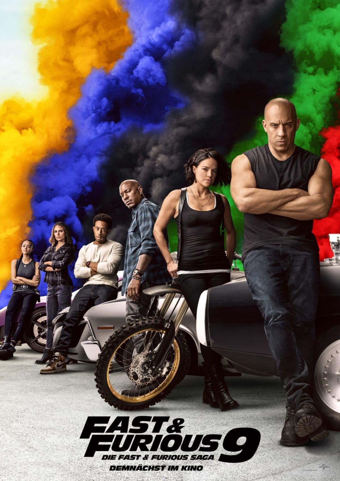 Vin Diesel, Michelle Rodriguez und vier weitere Personen aus Fast & Furious 9 stehen vor ihren Rennfahrzeugen. Im Hintergrund steigt bunter Rauch auf. Das Franchise soll nach elf Filmen der Hauptreihe beendet werden - unser Filmtoast Newsbrunch.
