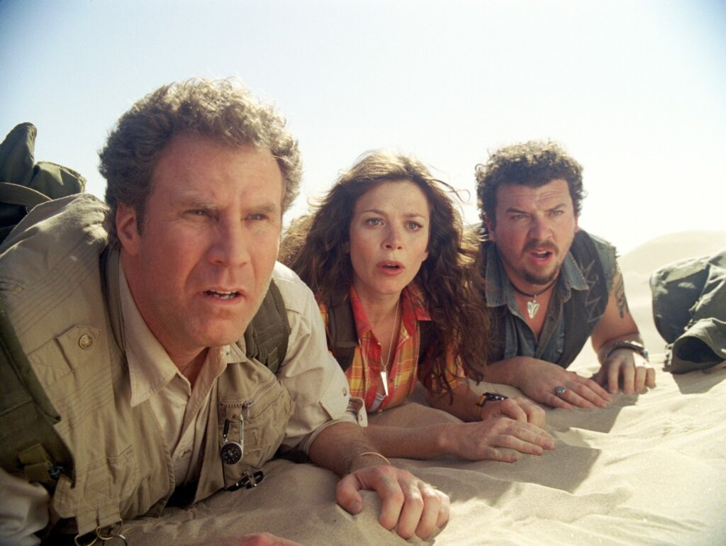 Will Ferrell als Rick Marshall, Anna Friel als Holly und Danny R. McBride als Will Stanton liegen nebeneinander im Wüstensand und beobachten etwas.