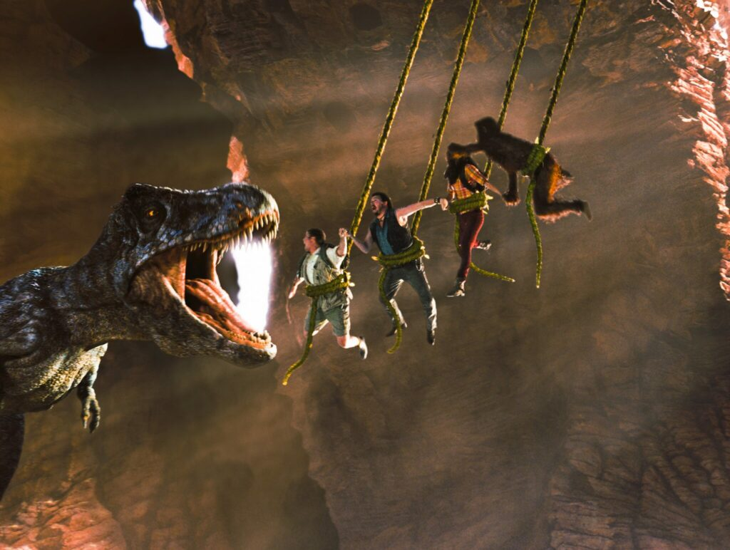 Rick Marshall, Will Stanton, Holly und Affenmann Cha-Ka schaukeln in einer Höhle an Lianen und versuchen dem weit geöffneten Maul des T-Rex zu entkommen.