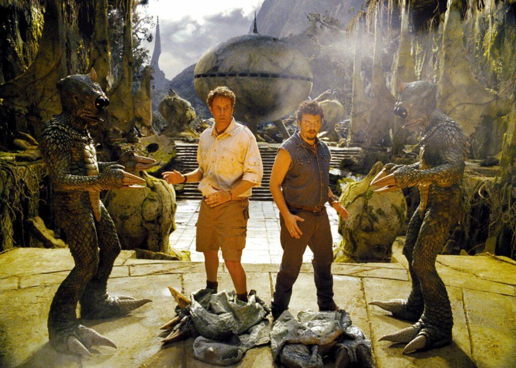 Zwei froschähnliche Sleestaks bedrohen Marshall und Stanton von zwei Seiten in einer grünschuimmernden Fantasykulisse in Die fast vergessene Welt.