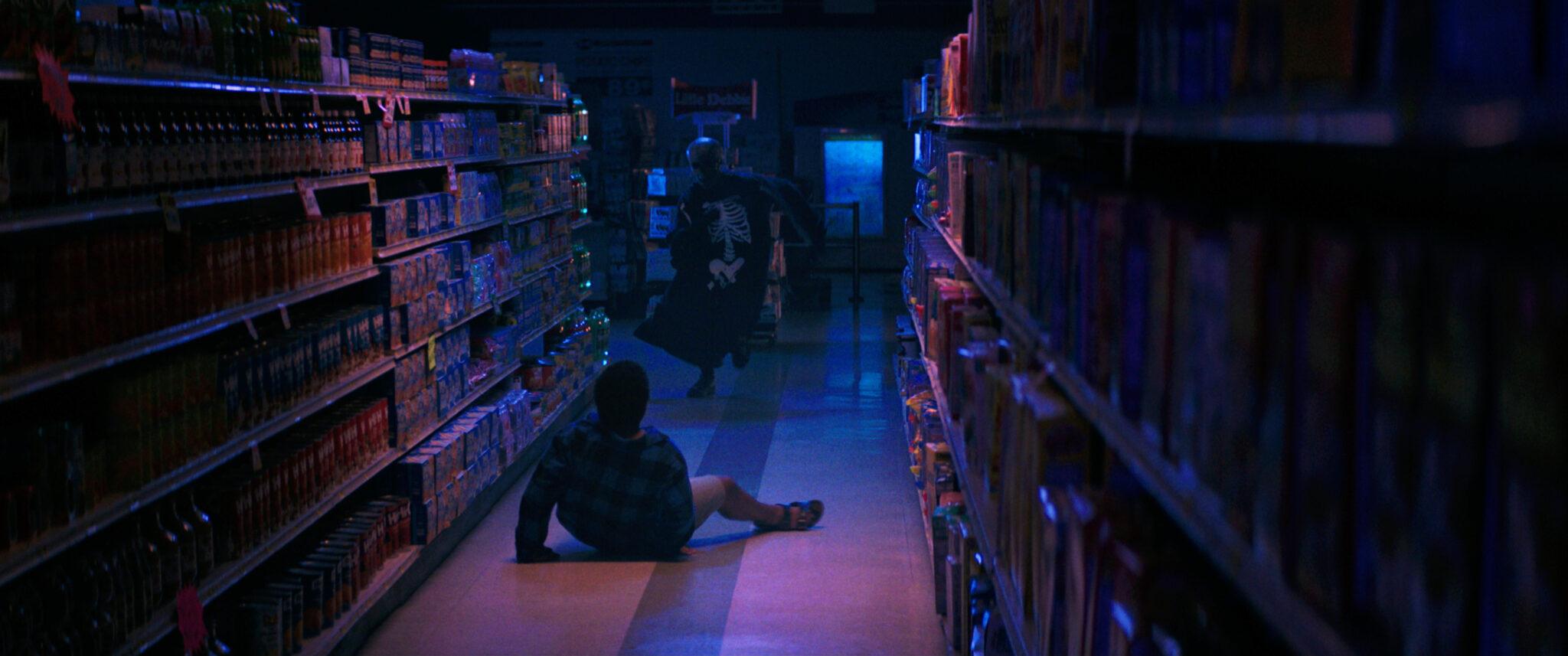 Josh liegt in Fear Street Teil 1 zwischen zwei Supermarktregalreihen auf dem Boden. Auf ihn zu rennt ein Mann mit Skelettkostüm und Messer in der Hand.