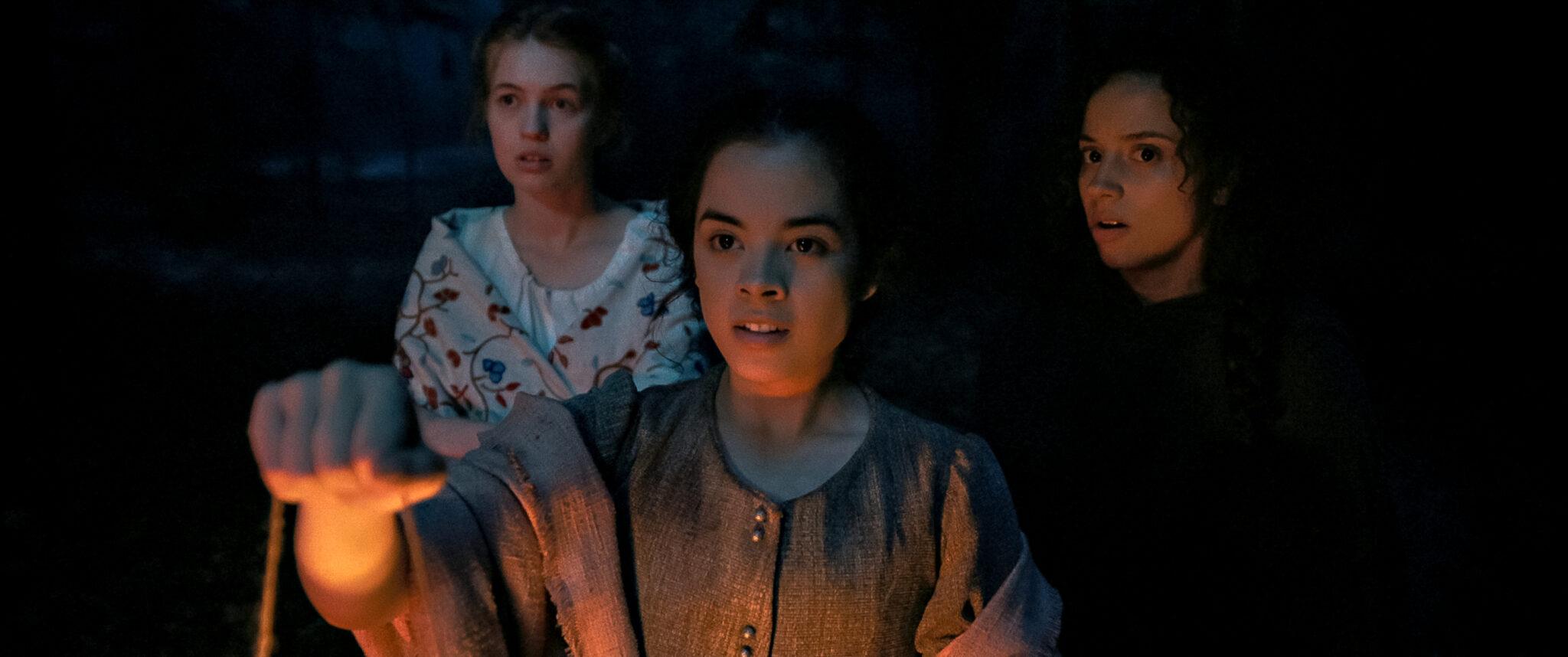 Hannah, Lizzie und Sarah im Dunkeln. Nur eine Laterne erhellt ihre Gesichter.