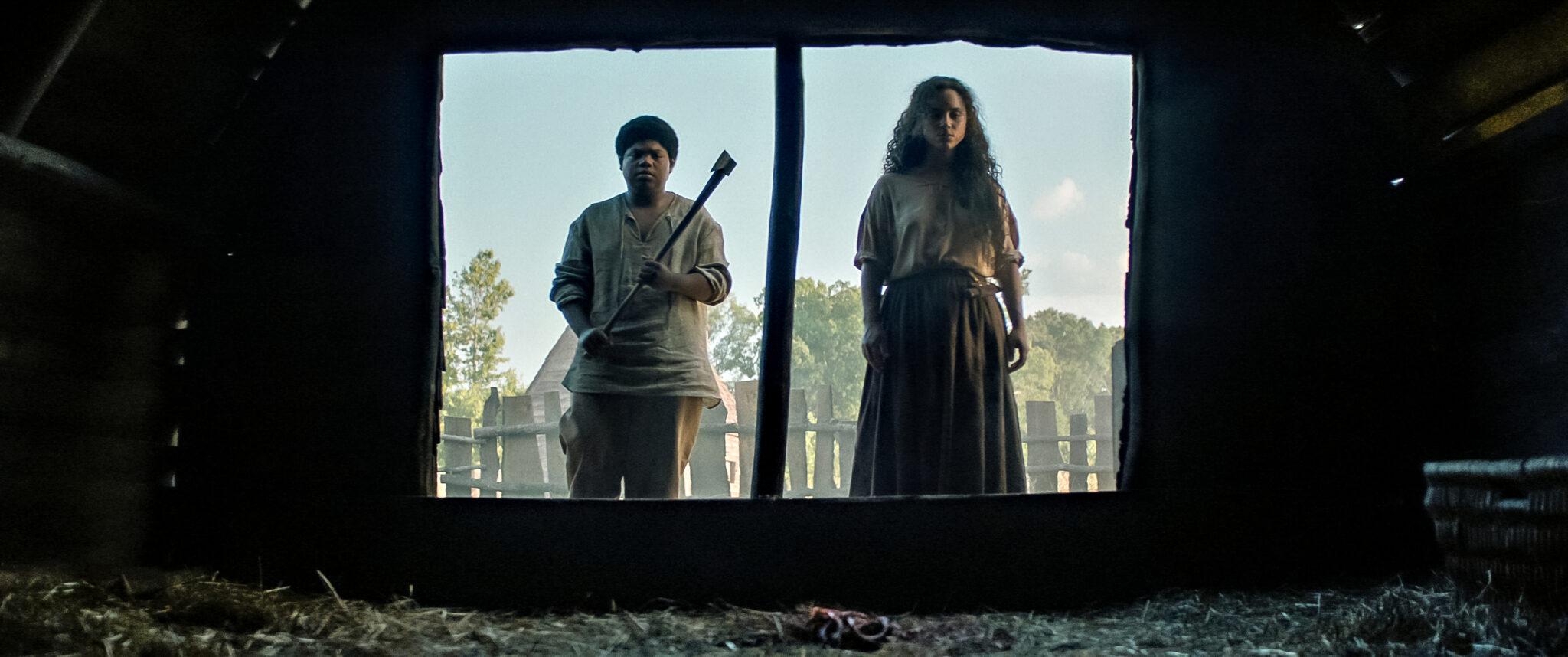Henry (Benjamin Flores Jr. ) und Sarah Fier (Kiana Madeira) stehen vor einer Scheune und schauen nach innen. Er trägt eine Axt. Beide haben altertümliche Outfits an.
