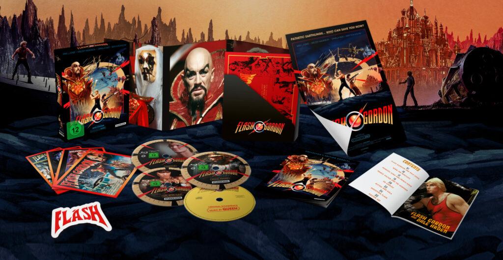 """Das Bild zeigt den Inhalt der Collector's Edition. Unter anderem sind vier Discs zu sehen, wovon drei schwarz und eine gelb ist. Des Weiteren erkennt man einige Motive auf der Verpackung, wie Bösewicht Ming, sowie vereinzelnd Postkarten, einen Aufnäher mit dem Schriftzug """"Flash"""" und ein Poster."""