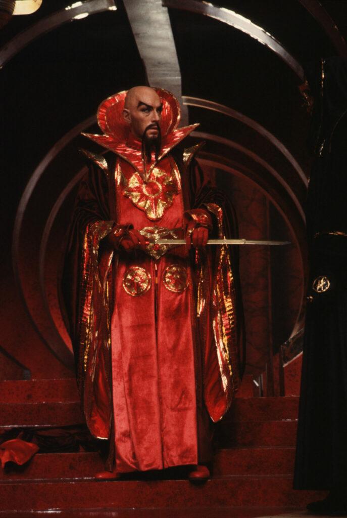 Ming steht in seinen leuchtend roten Gewändern vor einem seiner Schwergen. Der Bösewicht trägt Glatze, ebenso einen spitz zulaufenden schwarzen Kinnbart. Er hält eine goldene lange Klinge waagerecht in seinen Händen.