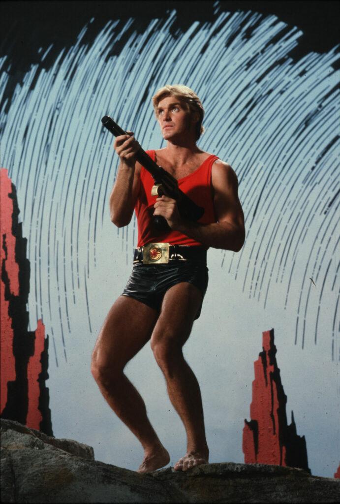 Flash Gordon steht leicht in die Knie gebeugt vor einem hellblauen Hintergrund. Er trägt eine kurze enganliegende schwarze Hose und ein ebenfalls enges ärmelloses rotes Shirt. Er hält eine Schusswaffe in den Händen.