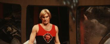 Flash Gordon stehe in ärmellosen schwarz-roten Shirt vor einigen Trümmern. In seiner rechten Hand hält er ein goldenes Schwert und blickt auf etwas nach unten.