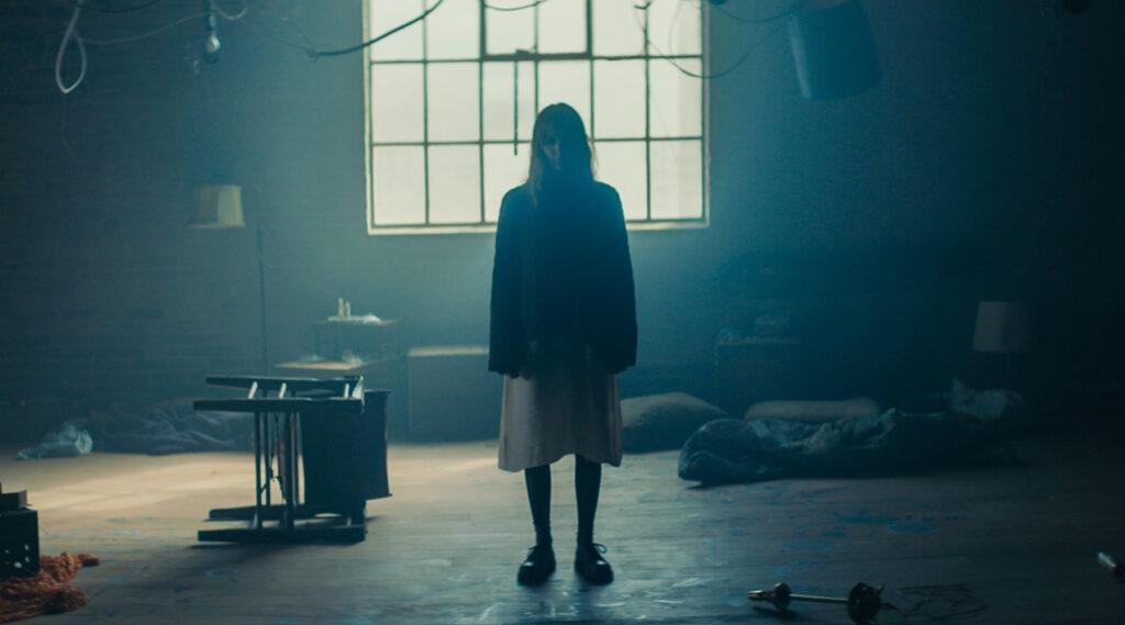 In der Mitte des Bildes und somit in einer vermeintlich alten Lagerhalle steht Freds Schulfreundin Conny erscheint in Freds Flashbacks. Sie ist kaum zu erkennen und man erkennt nur eine weibliche Silhouette.