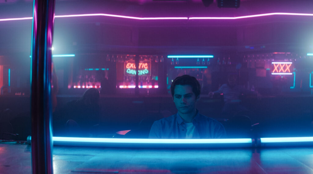 Fred ist allein in einem Nachtclub. Es ist dunkel und pinke - blaue Neonlichter erlebten das Lokal. Er befindet sich in der Mitte des Bildes und wirkt in sich gekehrt.