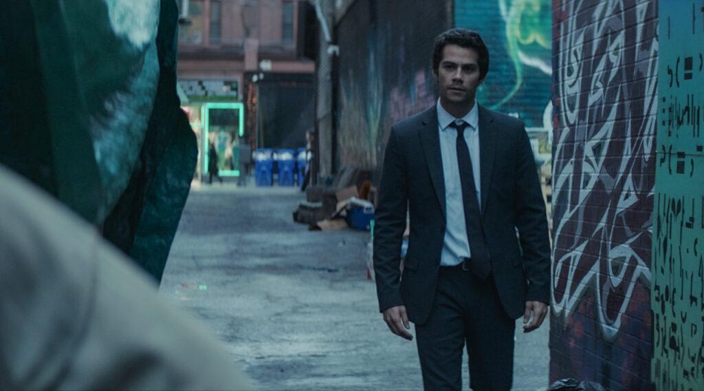 Fred ist in einer schmuddeligen Gegend unterwegs und trägt einen Anzug mit Krawatte. Er wirkt entschlossen und schaut nach vorn.
