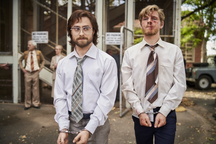 Daniel Radcliffe und der blutende Daniel Webber stehen in Handschellen vor einem Regierungsgebäude, hinter ihnen sind Demonstranten zu sehen - Neu auf Sky im August 2021