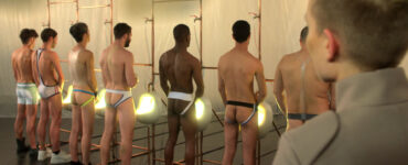 Mehrere nackte Männer stehen mit dem Rücken zur Kamera und onanieren in Becken - Fluidø