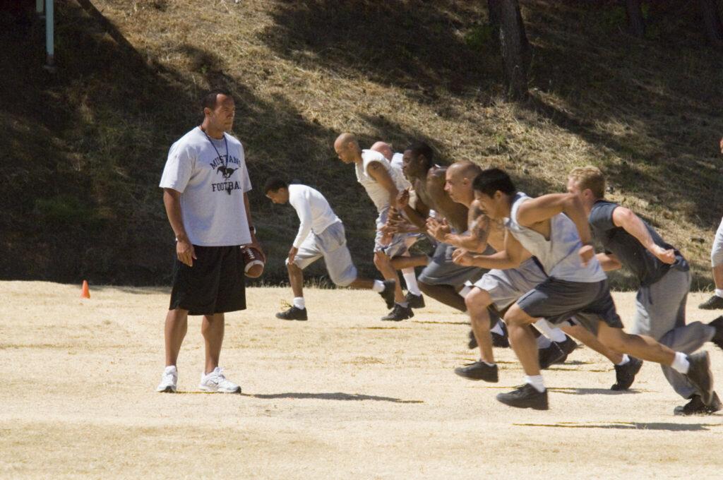 Football Filme: Sean Porter (Dwayne Johnson) steht mit Trillerpfeife auf dem sandigen Trainingsplatz während die Spieler laufen müssen.