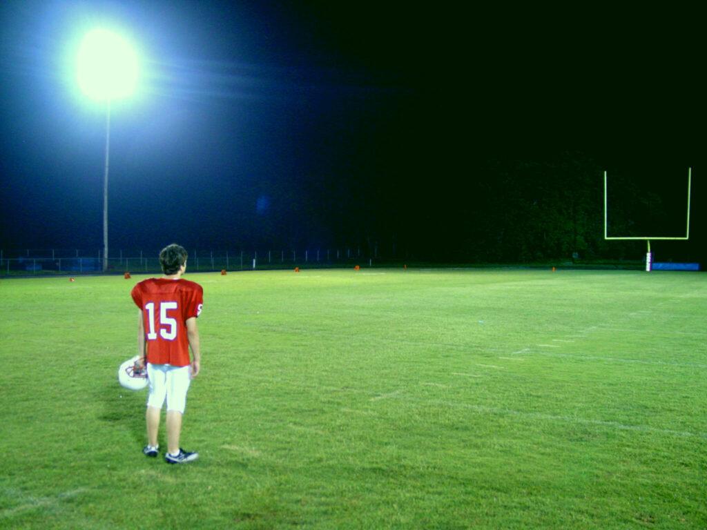 Ein Junge in rotem Footballtrikot und der Nummer 15 steht einsam auf dem großen Footballfeld und blickt in die Weite zu den Torpfosten. Die Scheinwerfer sind an. Football Filme