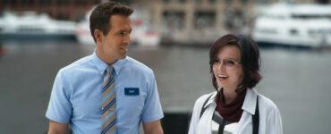 """Auf dem Bild sieht man Ryan Reynolds und Jodie Comer in ihren Rollen als Guy und Molotov Girl. Guy trägt seine Arbeitskleidung, also ein hellblaues Hemd mit Krawatte und seinem Namensschild. Er blickt zu Molotov Girl und lächelt sie an. Diese trägt ihr Gameroutfit, welches auf einem weißen Hemd, einigen Accessoires sowie der obligatorischen Heldenbrille besteht. Sie lacht mit Blick nach vorne. - """"Free Guy"""""""