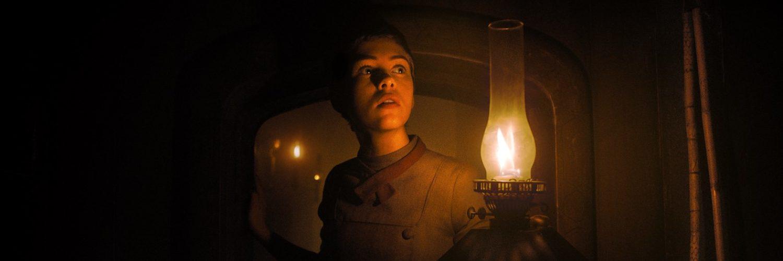 Gretel (Sophia Lillis) durschreitet mit einer Lampe die geheimnisvollen Gänge des Hexenhauses
