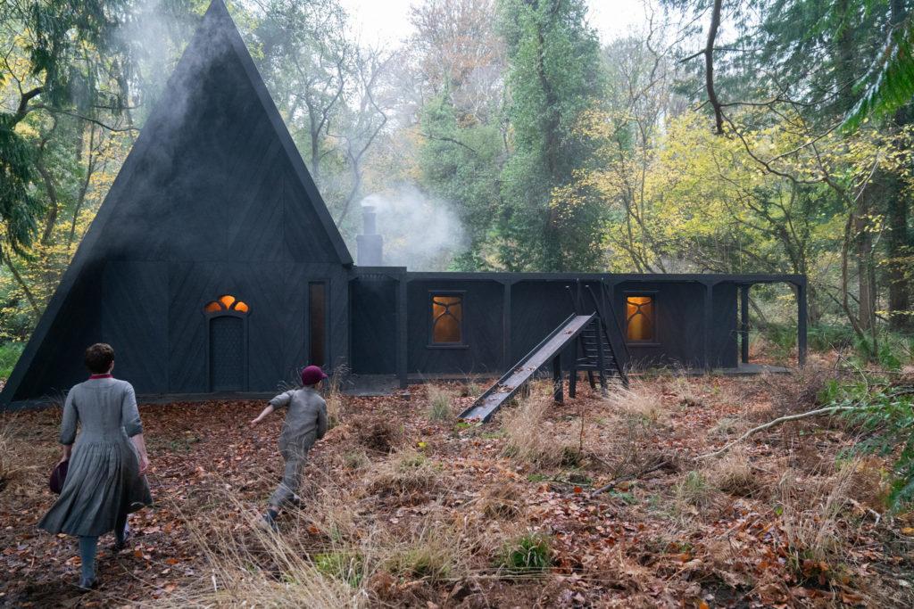 Gretel (Sophia Lillis) und Hänsel (Samuel Leakey) laufen in Gretel & Hänsel direkt auf das Hexenhaus hinzu. Dieses steht mitten im Wald und beeindruckt mit seiner dreieckigen Form und es steigt Rauch aus dem Kamin.