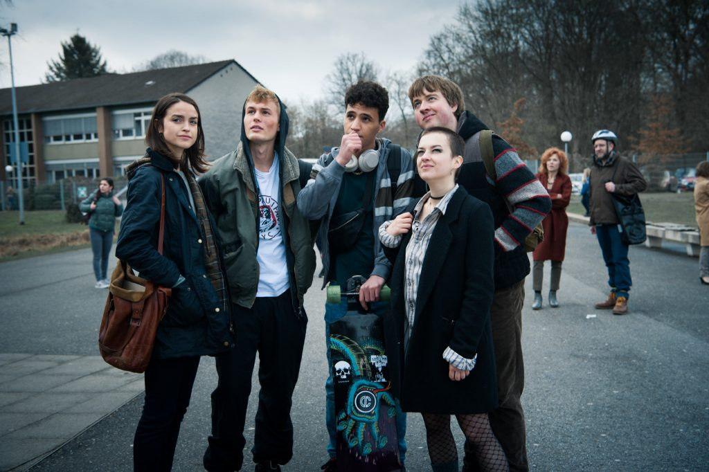 Gruppe junger Menschen auf einer Straße, blicken in den Himmel