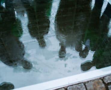 Besucher spiegeln sich im Glas einer Holocaust-Gedenkstätte | Germans & Jews - Eine neue Perspektive.