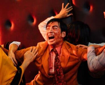 """Der mit Blut überzogene Wang schützt sich und eine hyterische Frau hinter ihm vor zwei Zombies. Der Name """"Get the hell out"""" wird Programm."""