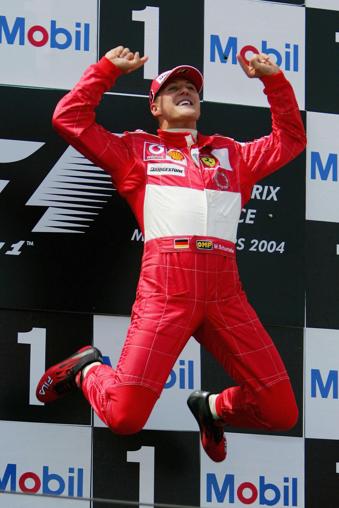 Michael Schumacher im roten Renn-Overall springt vor einer Reklamewand mit gestreckten Armen in die Luft