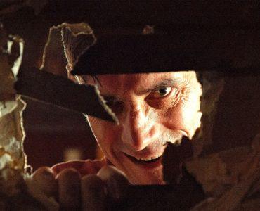 Don Koch (C.M. Punk) schaut wahnsinnig durch ein Loch in der Wand