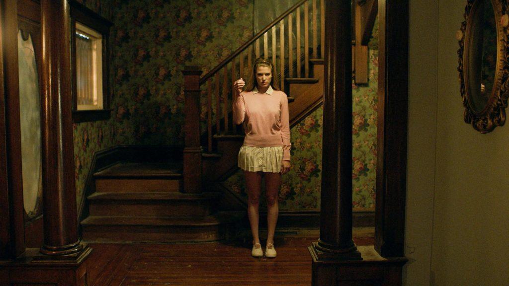 Eine junge Frau steht bedrohlich dreinblickend vor einem Treppenaufgang im alten Haus.