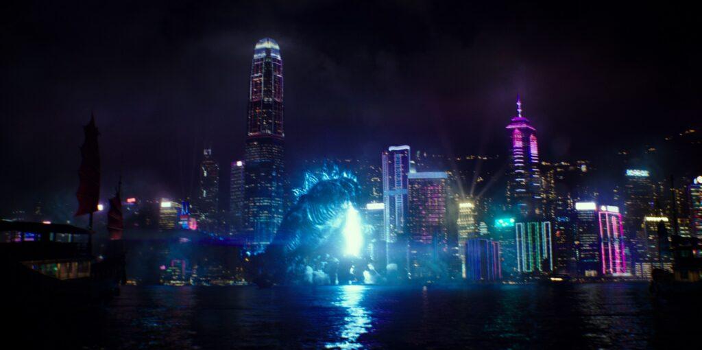 Godzilla richtet seinen Atomatem vor der Skyline von Hong Kong gegen die Erde