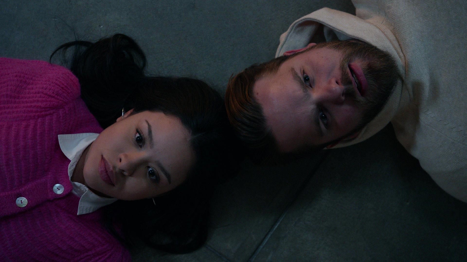 Ein Mädchen und ein Mann liegen Kopf an Kopf auf dem Boden