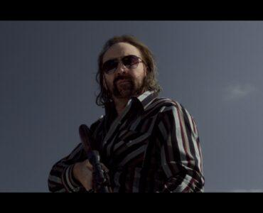 Walter (Nicolas Cage) steht mit Sonnenbrille und Gewehr auf dem Dach und blickt hinab zu seinem potentiellen Opfer.
