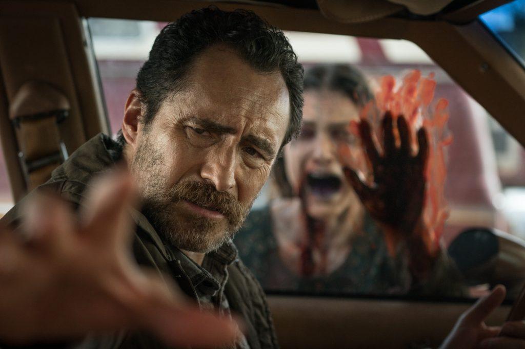 Goodman sitzt im Auto und vor der Scheibe erscheint ein Geist in The Grudge