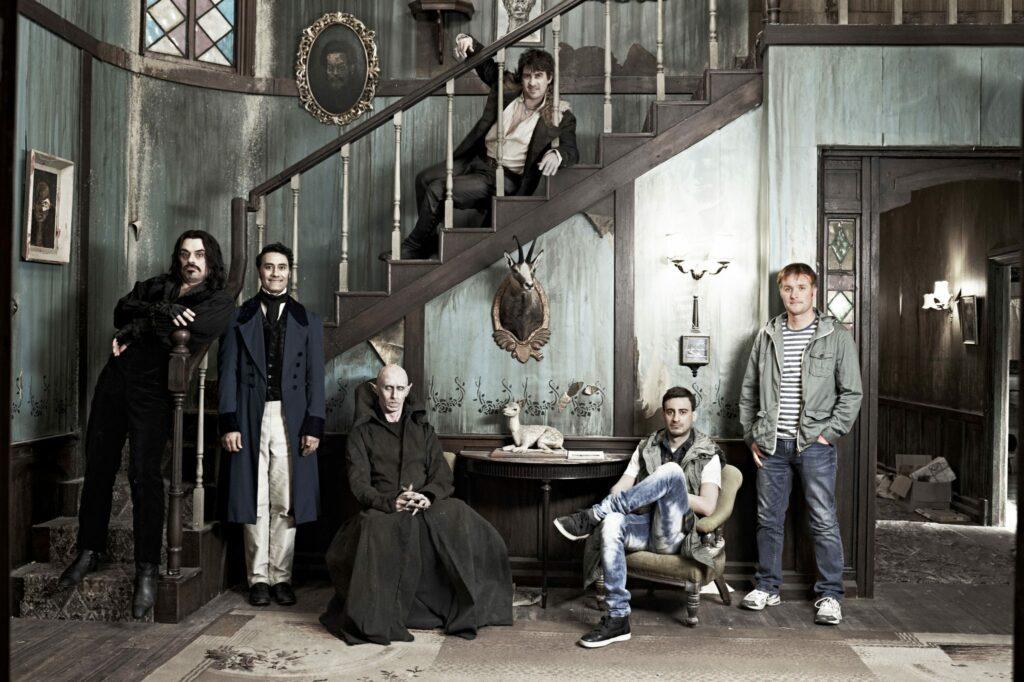 """Der deutsche Filmtitel lautet """"5 Zimmer, Küche, Sarg"""", der des Originals """"What we do in the Shadows"""". Auf dem Bild sieht man die Mitglieder der WG vor einer Wand für ein Foto posieren. Oberhalb der Wand ist eine Treppe, die von links unten nach rechts oben führt, wo auch einer der Vampire sitzt, während der Rest unten steht oder sitzt. Zwei stehen links, vor ihnen sitzt einer. Ein weiterer sitzt rechts und neben im am Rand des Bildes steht der einzige Mensch der WG."""