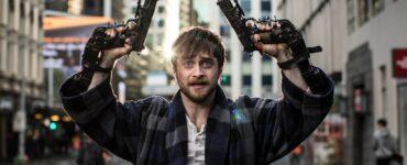 Daniel Radcliffe in Guns Akimbo mit erhobenen Händen, an den jeweils eine Waffe festgeschraubt ist