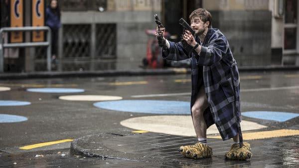 """Auf dem Bild ist Miles (Daniel Radcliffe) in """"Guns Akimbo"""" zu sehen. Er steht an einem Bürgersteig und blickt mit verängstigten und Hilfesuchenden Blick auf jemanden außerhalb des Bildes. In seinen Händen sind die beiden Pistolen zu erkennen, die an ihm befestigt worden. Außerdem erkennt man die Wunden außerhalb seiner Hände. Er trägt einen karierten Bademantel und zumindest keine lange Hose, da seine nackten Beine zu sehen sind. Des Weiteren trägt er Tigertatzen-Hausschuhe."""