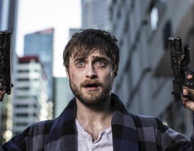 """In """"Guns Akimbo"""" spielt Daniel Radcliffe Miles. Dieser schaut auf dem Bild sehr verängstigt. Dabei hebt er seine Hände beide in die Höhe, in denen sich die beiden Pistolen befinden. Die Finger sind mit Schrauben an den Waffen befestigt."""