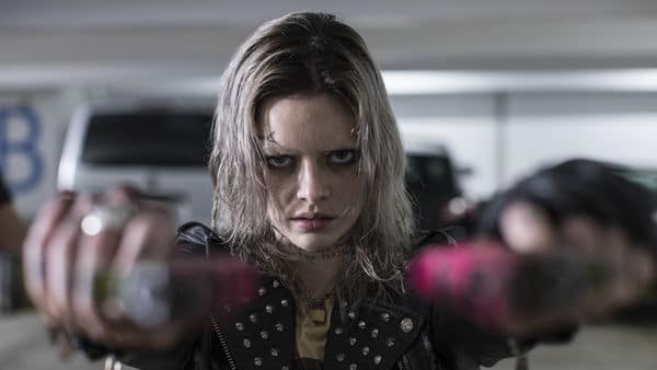 """Auf dem Bild ist Samara Weaving als Nix im """"Guns Akimbo"""" zu sehen. Diese blickt mit finsterer Miene direkt auf den Betrachter. Oberhalb ihrer rechten Augenbraue und am Hals sind mehrere verschiedene Tätowierungen zu erkennen. Sie hält zwei Pistolen seitlich geneigt in beiden Händen und zielt auf den Betrachter."""
