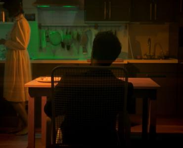 """Ein Mann mit dem Rücken zur Kamera sitzt an einem Küchentisch während eine Frau (Anna Heidegger als Maria) in der Küche zugange ist in """"Hager""""."""