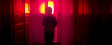 """Ein kleiner Junge, der sich mit dem Rücken zur Kamera im Flur eines Hauses der Haustür nähert, durch die von außen rotes Licht hereindringt, ist in """"Hager"""" zu sehen."""