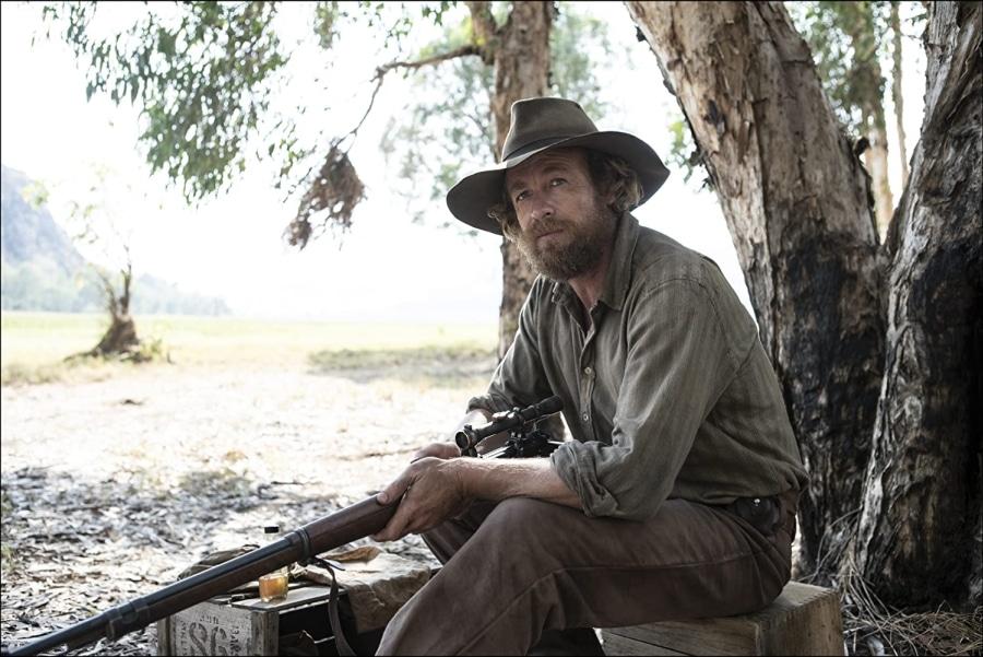 Simon Baker hockt bärtig und mit dem Gewehr in der Hand im Schatten eines Baumes zur Rast in High Ground - Der Kopfgeldjäger