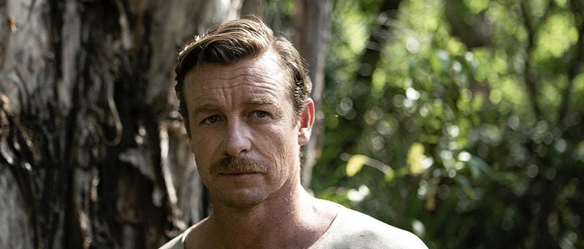 Simon Baker mit Schnurrbart und kurzen Haaren schaut missmutig drein in High Ground.