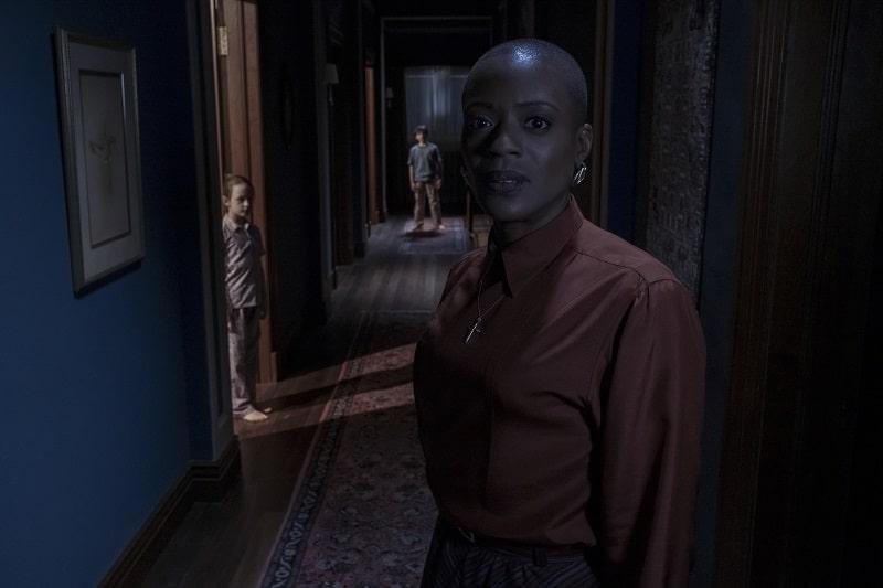 Eine afro-amerikanische Frau schaut verstört, hinter ihr ein Flur, in einer Tür steht ein Kind, genauso am Ende des Flurs in Spuk in Bly Manor - Neu auf Netflix im Oktober 2020